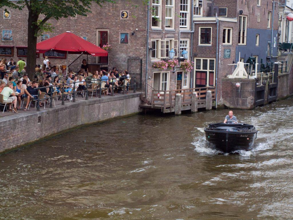 Günstig Essen in Amsterdam, Grachtenfahrt kleines Boot. Grachtenfahrt Amsterdam Abends. Wasserstraßen Niederlande.