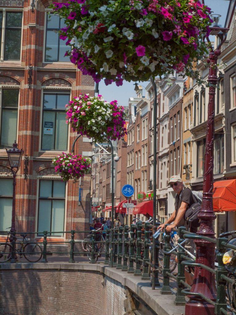 Fast wie in Venedig: Holland's Brücken, reich geschmückt mit Blumen. George geniesst den Blick über die Grachten von Amsterdam. Lies weiter über unsere Amsterdam: Sehenswürdigkeiten Reisetipps